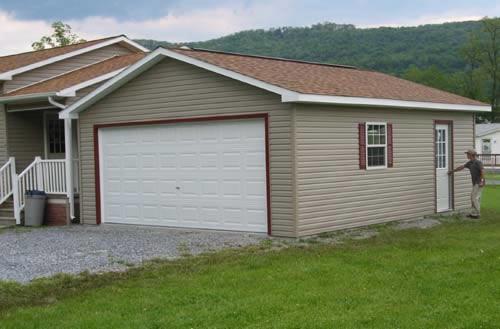 Гараж около дома из железобетонных плит, отделанный снаружи сайдингом.