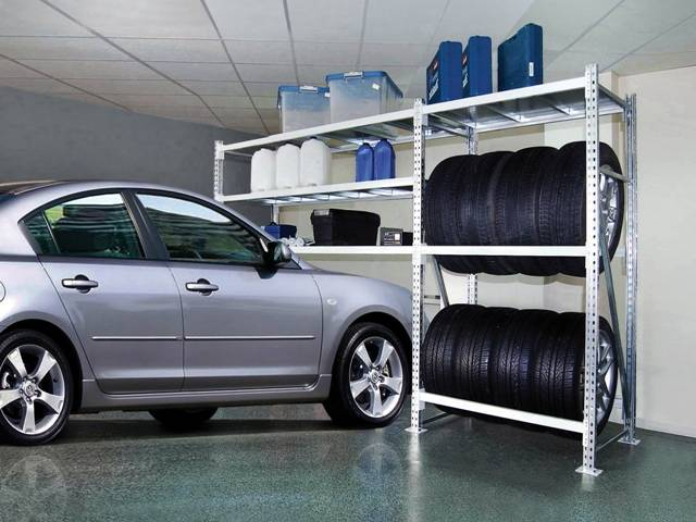 Комбинированный металлический стеллаж с полками для хранения вещей и вертикального складирования колес.