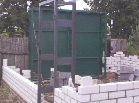 В процессе возведения стен установите несущие элементы ворот и дверей