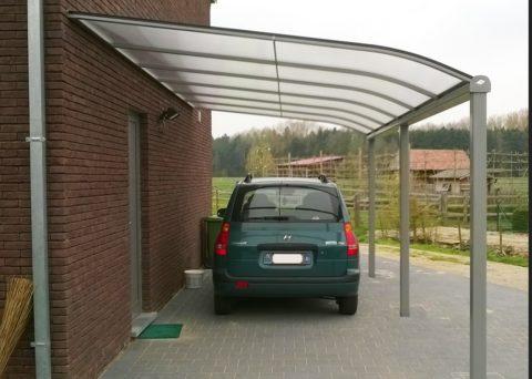 Навесы из поликарбоната во дворе для машины, пристроенные к стене здания